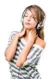 Beautiful  brunette immersed in music, eyes closed. Beautiful young brunette immersed in music wearing headphones, eyes closed, isolated on white background Royalty Free Stock Images