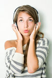 Beautiful brunette iwearing headphones, whistling. Stock Photos