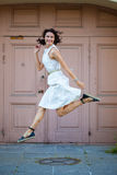Beautiful brunette  jumped in a white dress Royalty Free Stock Photos