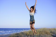 Beautiful brunette jumping in the beach Royalty Free Stock Photography