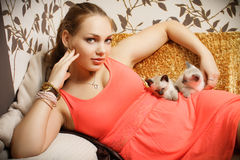 Beautiful brunette with kittens. Beautiful brunette in red dress  with kittens lying on the couch in a interior, fashion photography, studio light Stock Photography