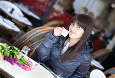 Beautiful brunette lady drinking coffee. In Parisian street cafe Royalty Free Stock Photography