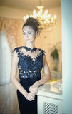 Beautiful brunette lady in elegant black lace dress posing in a vintage scene. Young sensual fashionable woman. With creative hairstyle indoor. Attractive slim stock photography