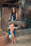Beautiful brunette lady feeding an elephant Royalty Free Stock Image
