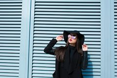 Beautiful brunette lady in stylish coat and hat posing near the. Beautiful brunette woman in stylish coat and hat posing near the shutter in sunny day Royalty Free Stock Image