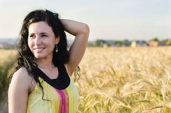 Beautiful brunette lady in wheat field. Portrait of beautiful smiling brunette woman in a wheat field at sunset Stock Photography