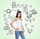 A beautiful brunette lady who is trying to make a choice in favour of a certain sport activity. Sport icons are drawn on the light Royalty Free Stock Photos