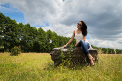 Beautiful brunette on a large boulder Royalty Free Stock Image
