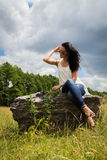 Beautiful brunette on a large boulder Royalty Free Stock Photography