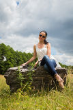 Beautiful brunette on a large boulder Stock Photos