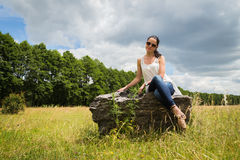 Beautiful brunette on a large boulder Stock Photography