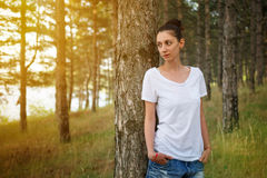 Beautiful brunette leaned against the pine tree and looking into the distance. Glare. Photo Stock Photography