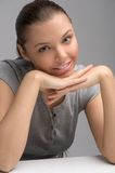 Beautiful brunette leaning on hands resting on table. Stock Photography