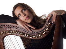 Beautiful brunette leaning on her classical harp Royalty Free Stock Photography