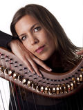 Beautiful brunette leaning on her classical harp Royalty Free Stock Image