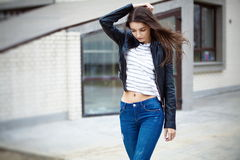 Beautiful brunette in leather jacket and jeans Stock Images