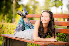 Beautiful brunette lies on bench Stock Image