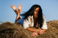 Beautiful brunette lies on haystack, autumn royalty free stock photo