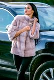 A beautiful brunette in a light-colored fur coat and black trousers is standing near a car on an autumn sunny day, sexually lookin stock photography