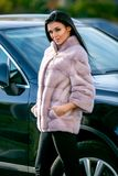 A beautiful brunette in a light-colored fur coat and black trousers is standing near a car on an autumn sunny day and is smiling s stock image