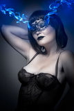 Beautiful brunette in lingerie, blue smoke coming out of the eye Royalty Free Stock Photos