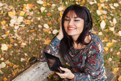 Beautiful brunette listens to the music through a digital tablet Royalty Free Stock Photography