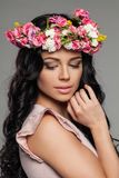 Beautiful Brunette with Lond Wavy Hairstyle. Makeup and Summer Flowers Stock Photo