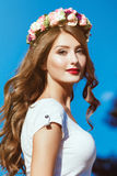 Beautiful brunette with long curly hair in a wreath of flowers p Royalty Free Stock Photography