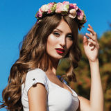 Beautiful brunette with long curly hair in a wreath of flowers Stock Photo