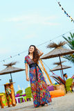Beautiful brunette in a long dress on the beach near the bar or go dancing. Concept of entertainment and recreation. Beautiful brunette in a colorful long dress Royalty Free Stock Image