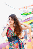 Beautiful brunette in a long dress on the beach near the bar or go dancing. Concept of entertainment and recreation. Beautiful brunette in a colorful long dress Stock Photography