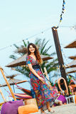 Beautiful brunette in a long dress on the beach near the bar or go dancing. Concept of entertainment and recreation. Beautiful brunette in a colorful long dress Royalty Free Stock Photo