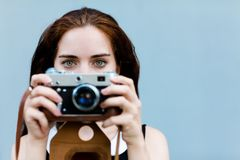 Beautiful brunette with long hair looking at the camera and holding in hands vintage camera. Close up. Stock Photos