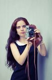 Beautiful brunette with long hair looking at the camera and holding in hands vintage camera. Colorful hipster photo Stock Image
