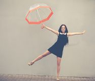 Beautiful brunette with long hair in a short black dress jumping under a transparent umbrella.Colorful hipster photo Stock Photography