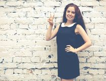 Beautiful brunette with long hair in a short black showing two fingers up near on background of white brick wall. Colorful hipster Royalty Free Stock Photos