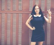 Beautiful brunette with long hair in a short black showing two fingers up near metallic brown fence. Colorful hipster photo Royalty Free Stock Image