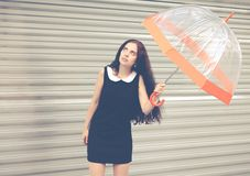 Beautiful brunette with long hair in a short black with an umbrella in her hands looking at the sky waiting for the rain. Colorful Royalty Free Stock Photos