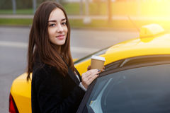 Beautiful brunette with long hair siting in yellow taxi Stock Photography