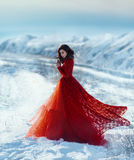 Beautiful brunette in a long scarlet outfit against the background of the winter landscape. Girl walks in the winter mountains.She dressed beautiful, lush, red royalty free stock photography