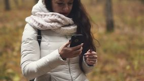 Woman tourist is looking for an address with a GPS navigator on a smartphone. Beautiful brunette is looking for an address with a GPS navigator on a smartphone stock video footage
