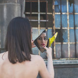 Beautiful brunette looking at herself in a mirror Royalty Free Stock Photography