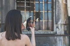 Beautiful brunette looking at herself in a mirror Royalty Free Stock Image