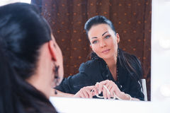 Beautiful brunette looking in the mirror Royalty Free Stock Photos