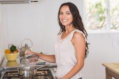 Beautiful brunette looking at saucepan Stock Image