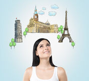 A beautiful brunette is looking up by dreaming about the visiting of the most famous european cities. The concept of tourism and s Royalty Free Stock Photo