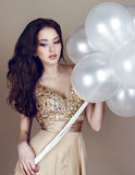 Beautiful brunette in luxurious beige dress holding a white balloons Stock Image