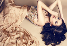 Beautiful brunette in luxurious sequin beige dress. Fashion studio photo of beautiful young girl with dark hair wearing luxurious beige dress,lying on the floor royalty free stock image
