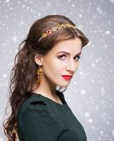 Close-up of gorgeous, young brunette with enigmatic face wearing. Beautiful brunette with luxury golden necklace over grey winter background. Christmas concept Royalty Free Stock Photos