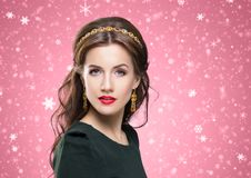 Portrait of gorgeous brunette wearing luxury golden coronet and. Beautiful brunette with luxury golden necklace over red winter background. Christmas concept Royalty Free Stock Photography